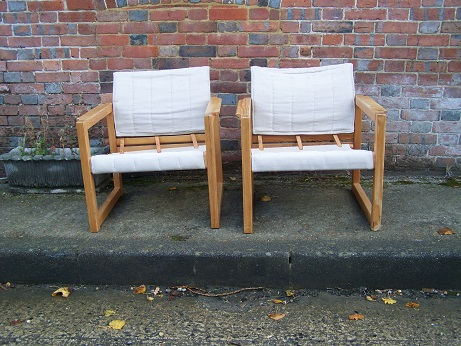 A pair of vintage canvas covered chairs for restoration.