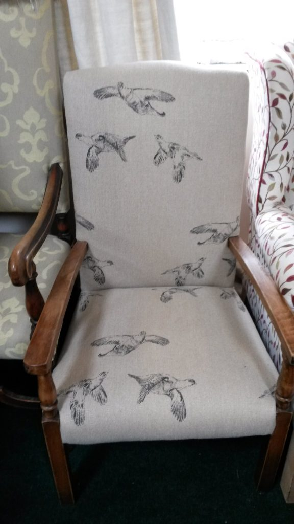 Open armed chair covered in heavy linen with bird print.