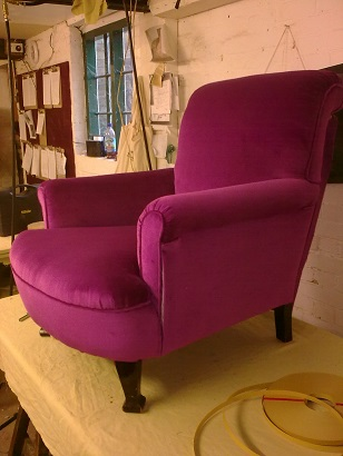 traditionally upholstered Edwardian armchair, in magenta velvet.