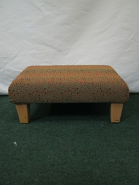 small footstool covered in a spot-weave chenille.